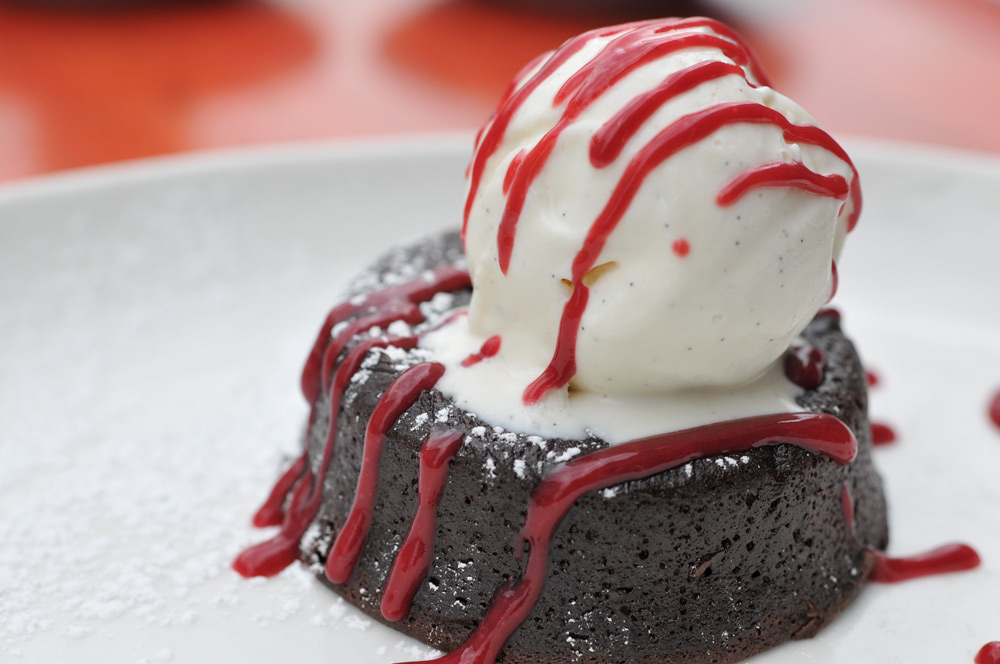 Chocolate cake topped with ice cream and raspberry sauce