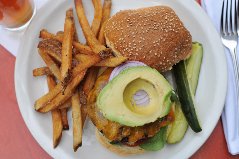 Cheeseburger and fries topped with avocado and onions, with a side of pickles