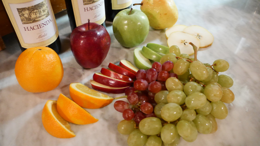 Fresh fruit paired with wine bottles